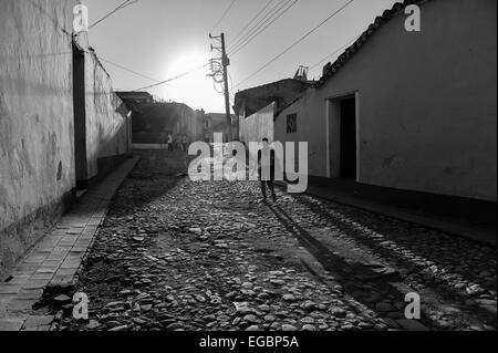 Una figura oscura a camminare su una strada di ciottoli in Trinidad, Cuba. Foto Stock