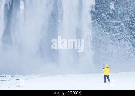 Turista in giacca gialla a cascata Skogafoss in inverno Skogar Sud Islanda Islanda Europa Foto Stock