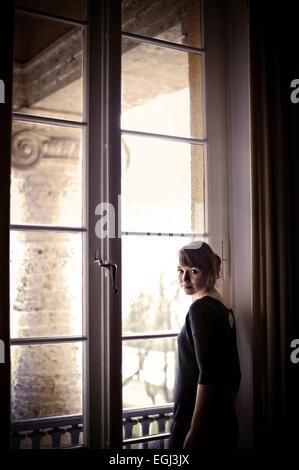 Giovane donna alla finestra, Foto Stock