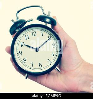 Un uomo con una meccanica sveglia nella sua mano con un effetto retrò Foto Stock