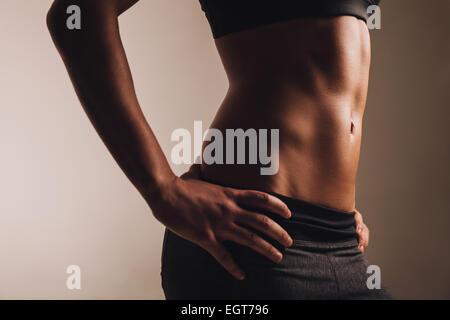 Close-up shot di giovane donna con cintura muscolare dei muscoli addominali. Abs di montare atleta femminile. Foto Stock