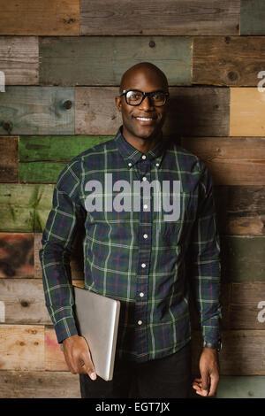 Ritratto di giovane studente africano con computer che sorride alla telecamera. Bald giovane uomo che indossa gli occhiali in piedi contro una parete in legno. Foto Stock