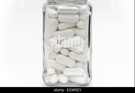 Compresse bianche in un piccolo vaso di vetro vicino fino Foto Stock