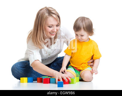 La madre e il bambino gioca con la costruzione di blocchi toy isolato su bianco Foto Stock