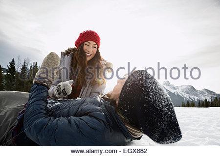 Giovane giocando in campo nevoso sotto la montagna Foto Stock