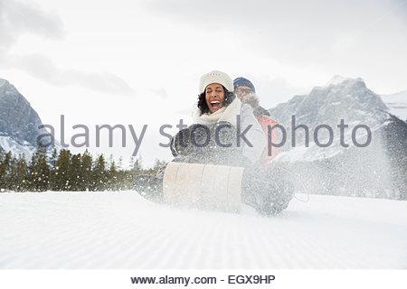 Coppia esuberante slittino nel campo nevoso Foto Stock