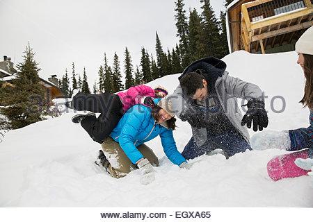 Famiglia giocoso godendo lotta con le palle di neve in campo nevoso Foto Stock