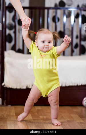 Il toddler prendendo i primi passi con la madre aiutare Foto Stock