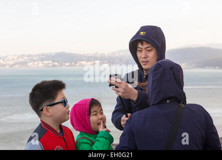 Uomo asiatico, utilizzando selfie stick, tenendo selfie foto, punto di vista, lato nord del Golden Gate Bridge, Foto Stock