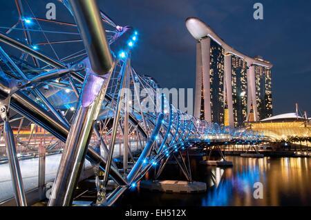 Singapore, Marina Bay, Marina Bay sands hotel progettato dall architetto Moshe Safdie in serata, vista dal ponte Foto Stock