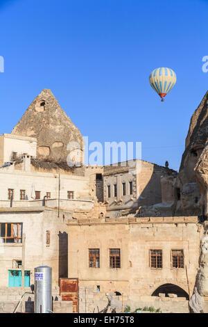 Mongolfiera Volare sopra antico camino fata abitazioni troglodite in cielo blu a Goreme, Cappadocia, Turchia Foto Stock
