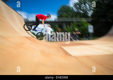 BMX Biker compiendo acrobazie durante la marcia su una rampa Foto Stock