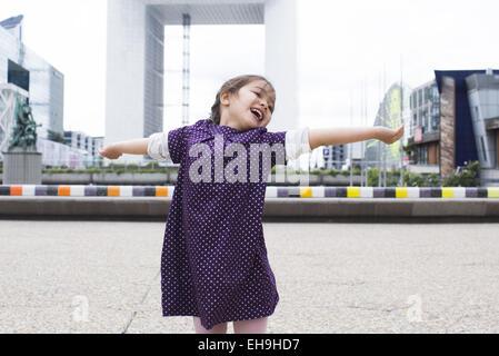 Bambina in piedi con la sua testa indietro e braccia tese davanti al Grande Arche, Parigi, Francia Foto Stock