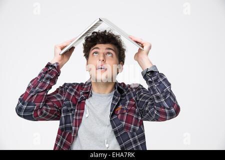 Uomo con notebook sulla sua testa come tetto di hous e guardando in alto Foto Stock