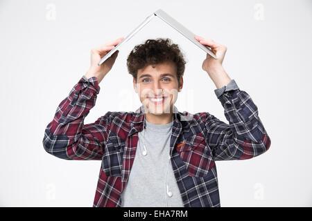Uomo felice azienda portatile su la sua testa come tetto di hous Foto Stock