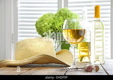 ... Bicchiere di vino con cappello di paglia sul tavolo Foto Stock 45f045f967fd