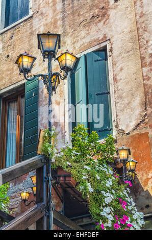 Vecchia facciata di edificio, persiane verdi, fiori e lampade in ombra con luci di posizione accese, Venezia , Italia. Foto Stock