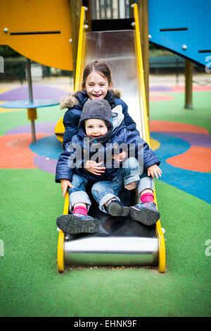 7 anno-vecchia ragazza e 18 mese-vecchio baby boy su una diapositiva in un parco giochi. Foto Stock