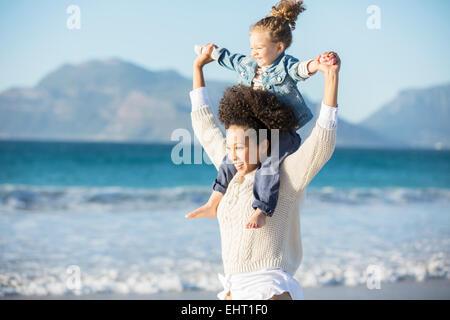 Madre figlia che porta sulle sue spalle sulla spiaggia Foto Stock