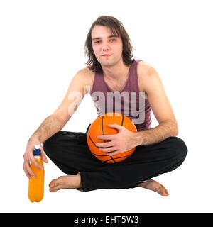 Uomo seduto sul pavimento con la pallacanestro e succo di arancia, isolata a sfondo bianco Foto Stock