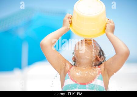 Ragazza sulla spiaggia gli spruzzi di se stessa con un secchio di acqua Foto Stock