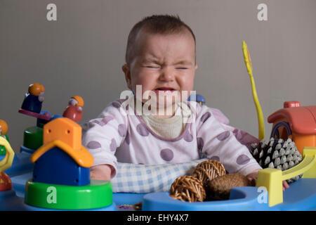 8 mese fa Baby girl, nella baby bouncer piangere Foto Stock