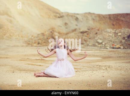 Ragazza seduta nel deserto con le braccia aperte Foto Stock