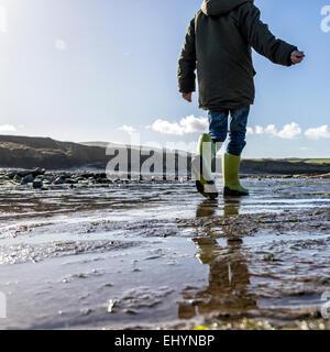 Basso angolo di visione di un ragazzo di camminare sulla spiaggia Foto Stock