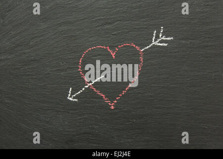 Chalk cuore con freccia disegnata su una scheda di Chalk.. Foto Stock