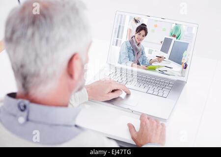 Immagine composita di closeup vista posteriore del grigio di un uomo dai capelli utilizzando laptop alla scrivania Foto Stock