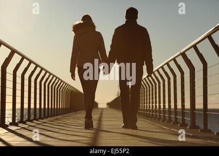 Torna la silhouette di un paio di camminare tenendo le mani su un ponte in spiaggia al tramonto Foto Stock