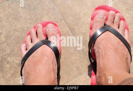 Piedi Mens in rosso flip-flop Foto Stock