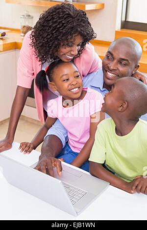 La famiglia felice che utilizza il notebook insieme