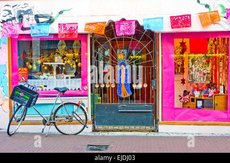 Luminose gli oggetti colorati e visualizza in un messicano & American themed store in Amsterdam, Paesi Bassi. Bicicletta Foto Stock
