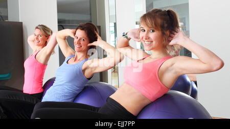 Tre donne fare esercizio su sfere nel centro fitness