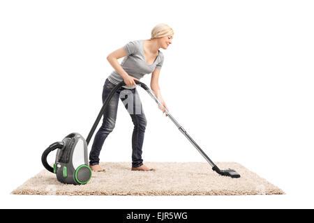 A piena lunghezza Ritratto di una donna di aspirare un color beige tappeto con un aspirapolvere isolati su sfondo bianco Foto Stock