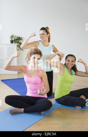 Donna sorridente muscoli di flessione su esercizio stuoie in studio