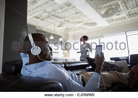 Uomo con le cuffie utilizzando il telefono cellulare sul divano Foto Stock