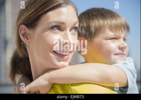Madre dando il suo figlio (6-7) piggyback ride Foto Stock