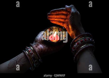 Donna mani con henna holding candela isolata su sfondo nero con tracciato di ritaglio Foto Stock