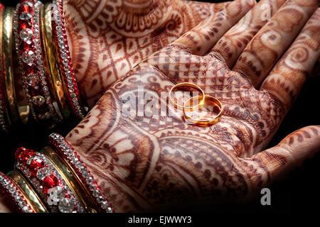 Donna mani con henna tenendo due golden gli anelli di nozze su sfondo nero Foto Stock