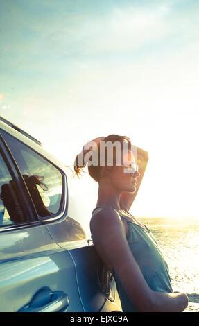 Donna appoggiata contro auto al tramonto da Ocean Foto Stock