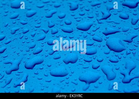 Gocce d'acqua sulla superficie blu Foto Stock