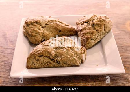 Pane appena sfornato, cannella e uvetta scones su un quadrato bianco piastra Foto Stock