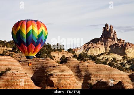 Una colorata mongolfiera pilioted da Dave Aley di Albuquerque vola vicino Chiesa Rock durante il Red Rock Rally a palloncino