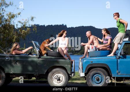 Amici adulti in chat sulla parte superiore dei veicoli off road, Lago Okareka, Nuova Zelanda Foto Stock