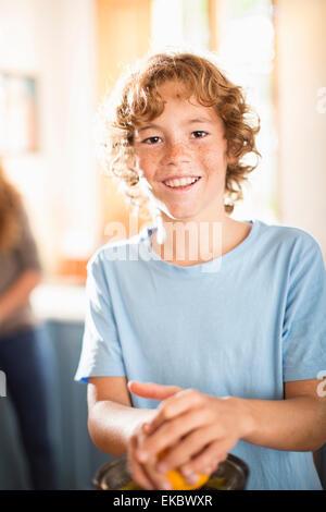 Ragazzo adolescente a spremere il succo arancia in cucina Foto Stock