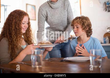 Madre che servono spaghetti ai bambini al tavolo da pranzo Foto Stock