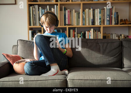 Ragazzo ascoltando musica su cuffie e con tavoletta digitale Foto Stock