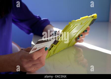 Ritagliato colpo di donna di effettuare il pagamento tramite carta di credito e la tavoletta digitale Foto Stock